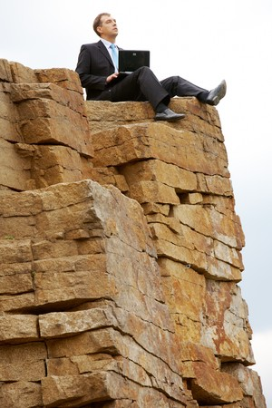 Thinking businessman with laptop sits on the top of mountain  photo