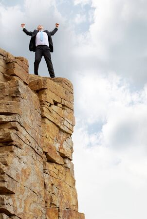 lucky man: excited business man standing on the mountain  Stock Photo