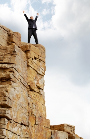excited business man standing on the mountain with raised arms photo