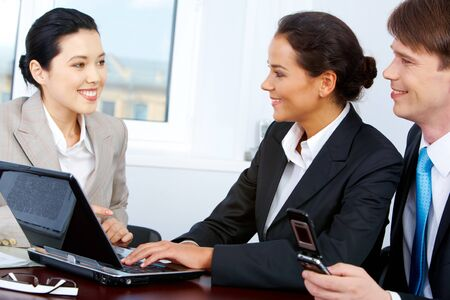 smart partners interviewing pretty Asian female in office Stock Photo - 7355554