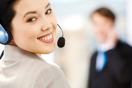 Portrait of attractive customer support service representative wearing headset photo