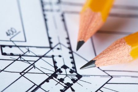 engineering: Close-up of blueprints with sketch of project on workplace and two pencils Stock Photo