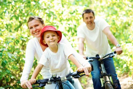family bike: Portrait of happy woman with son riding a bicycle in park on background of male