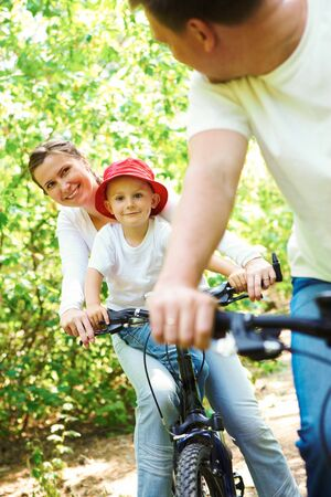 happy woman with son riding a bicycle in park while looking at her husband photo