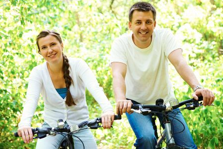 happy husband and wife riding bicycles outdoors photo