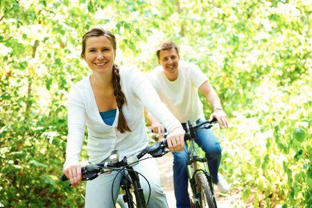 pareja saludable: bicicleta de equitaci�n de mujer feliz al aire libre junto a su marido en segundo plano