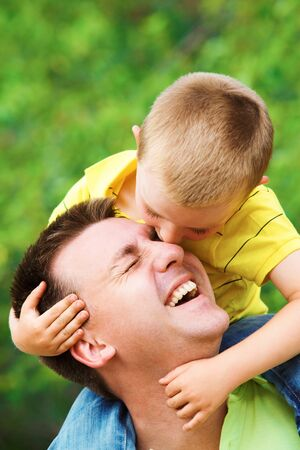 men s: Portrait of father cuddling his son during summer vacation