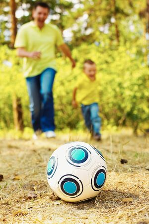 pastime: Image of ball on ground in park with running father and son at background