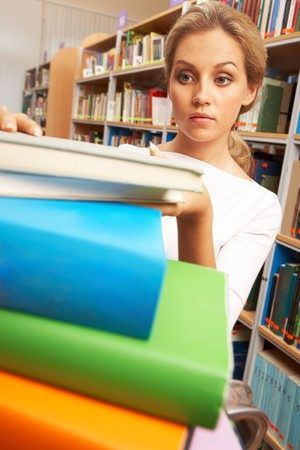 Image of smart student putting books in stack Stock Photo - 7409125