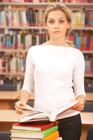 Image of teacher standing near table with books on it in the library  photo