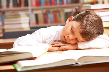 Image of young boy sleeping near books in the library  photo
