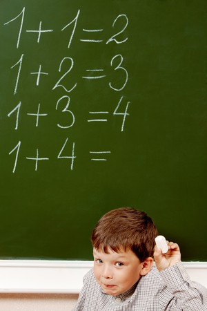 sums: Portrait of curious schoolchild standing at blackboard with written sums on it and looking at camera