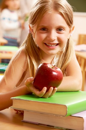 Portrait of happy pretty girl holding a red apple in the classroom    photo