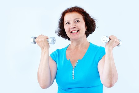 Portrait of middle-aged female doing physical exercise with dumbbells Stock Photo - 7409214