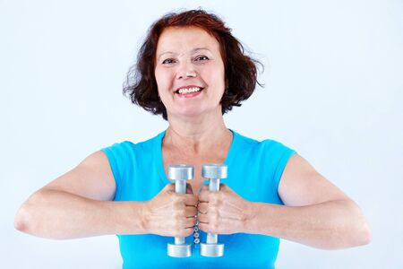 Portrait of middle-aged female doing physical exercise with dumbbells Stock Photo - 7409255