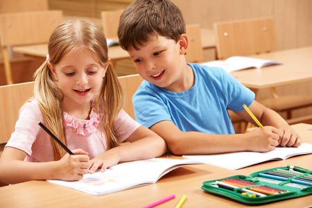 Mate: Portrait of two schoolchildren sitting by one desk during drawing lesson while boy looking at his mate's copybook