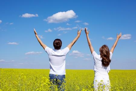 praising god: Vista posterior de j�venes de chico y chica alabando a Dios en la pradera amarillo en verano  Foto de archivo