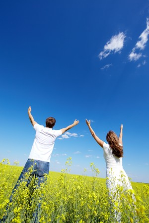 Back view of young guy and girl looking at sky with raised arms in yellow meadow