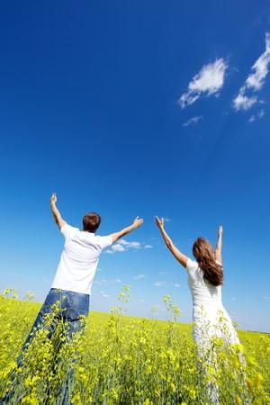 Rückansicht des jungen Guy und Mädchen Blick auf Himmel mit erhobenen Armen in gelbe Wiese  Standard-Bild