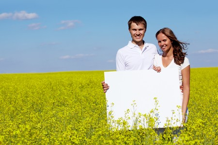 Portrait of happy young couple with blank paper standing in meadow  Stock Photo - 7409313