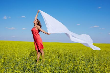 Image of happy woman holding a white fabric in the yellow meadow photo