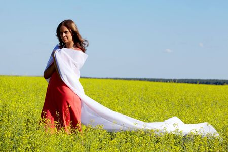 Image of happy woman folded in white fabric in the yellow meadow photo