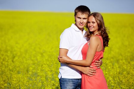 Image of happy couple in yellow meadow looking at camera while embracing Stock Photo - 7409317