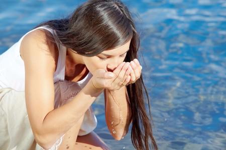 the thirst: Ritratto di una ragazza carina acqua potabile dalle mani dal fiume