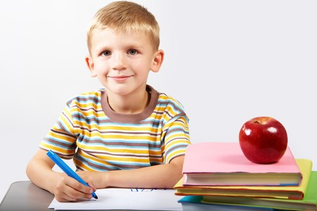 diligent: Diligent schoolboy looking at camera during drawing Stock Photo