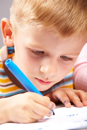 Close-up of school boy drawing picture