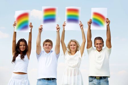 Portrait of happy girls and guys holding papers with rainbow parts outside