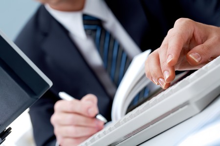 Close-up female�s hands touching keys of computer board on background of businessman making notes
