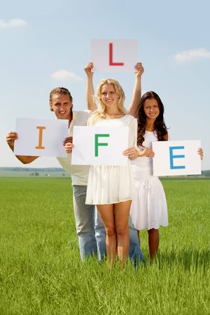 Portrait of happy friends holding papers with letters L, I, F, E while standing in green grass outside photo