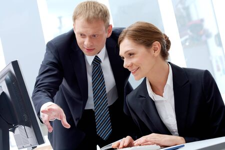 Successful businessman explaining something to his pretty colleague while they looking at monitor Stock Photo - 7409159