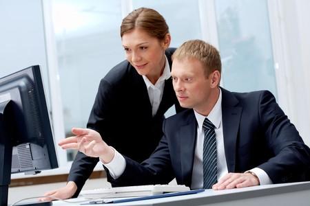 Succesvolle zaken man iets uit te leggen zijn mooie collega terwijl ze op zoek naar monitor  Stockfoto