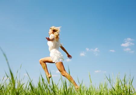 piedi nudi di bambine: Foto di ragazza felice che scende erba verde in giornata di sole