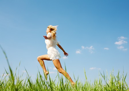 Photo of happy girl running down green grass on sunny day