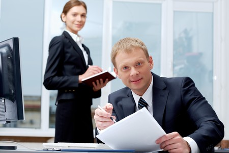 Portrait of confident boss holding papers at workplace with executive secretary standing behind Stock Photo - 7409109
