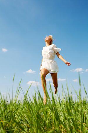 praterie: Foto di ragazza felice che scende erba verde in giornata di sole