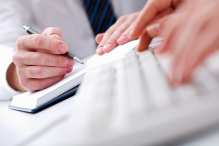 financial item: Close-up of male hands writing in notepad with typing secretary hands in front of him