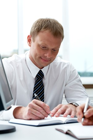 Portrait of businessman writing in notepad during work planning in office Stock Photo - 7409113