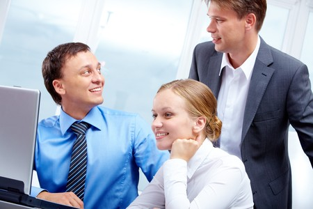 Portrait of two businessmen interacting while pretty employee looking at laptop near by Stock Photo - 7409286
