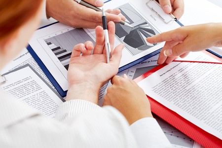 Close-up of business partners hands during discussion of papers Stock Photo - 7409292