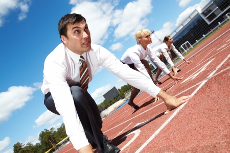 Row of business people getting ready for race with man at foreground Stock Photo - 7409314