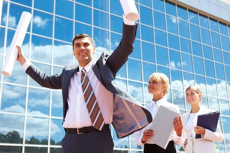 Portrait of successful leader holding rolled papers with two employees behind Stock Photo - 7409283