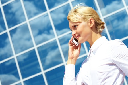 Portrait of pretty business leader talking by mobile phone with smile photo