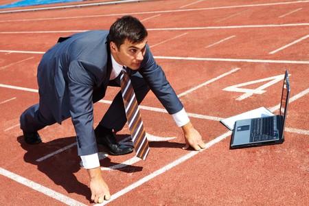 start of race: Imagen de hombre de negocios prepar�ndose para la carrera con el equipo port�til cerca por