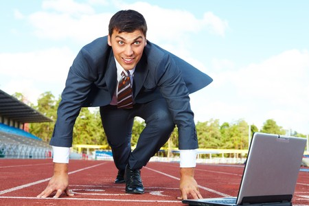 contestant: Image of businessman getting ready for race with laptop near by