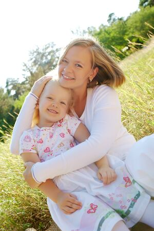 Portrait of mother embracing her daughter while sitting on grass Stock Photo - 7409397