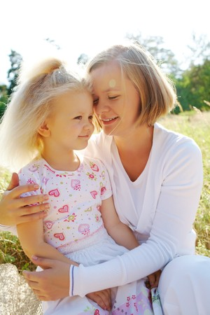 Portrait of mother embracing her daughter while sitting on grass photo